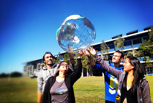 International students holding world globe