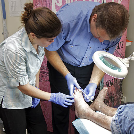 A doctor and USC nursing student treating a wound