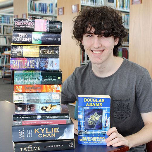 Jesse Highes with a stack of science fiction books