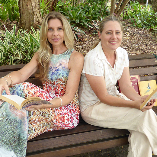 Maria Arena and Eileen Herbert-Goodall on a park bench with books