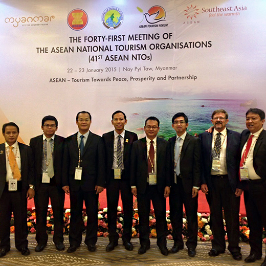 Eight men in suits stand under ASEAN tourism sign