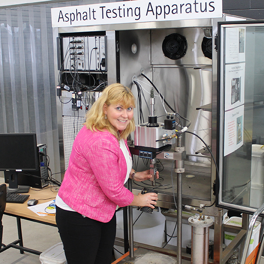 Susan Tighe holds a road core sample to the asphalt testing apparatis