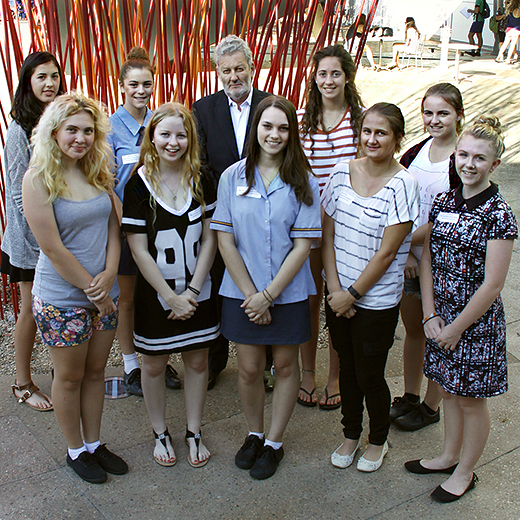 A group of nine students with Professor Robert Elliot standing in front of a sculpture