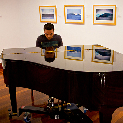 Timothy Morton-Rennalls playing a baby grand piano inside USC Gallery