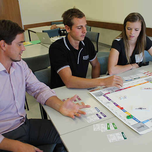 Lecturer Steven Boyd and students Jake Bendle and Samantha Boholt play the board game