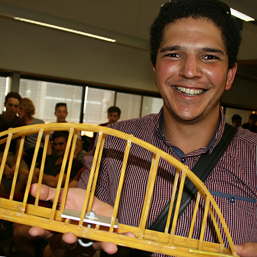 A student holding a bridge made out of spaghetti