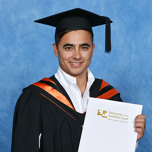 Boris Kimmel wearing graduation gown and mortar board holding his degree