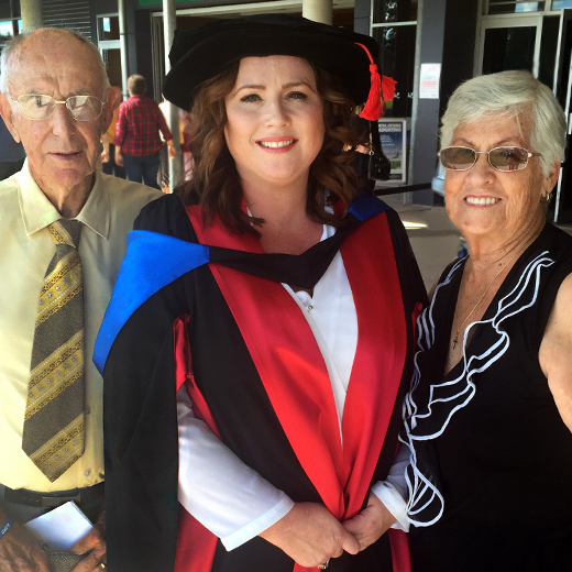 Jo Sparrow, in graduation cap and gown, with her parents