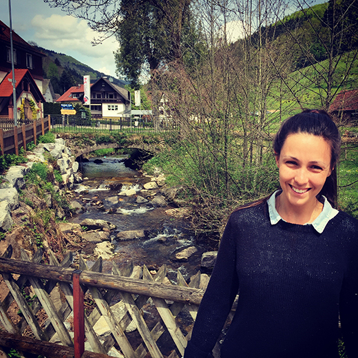 Kristin Caddell stands near a stream in a German village