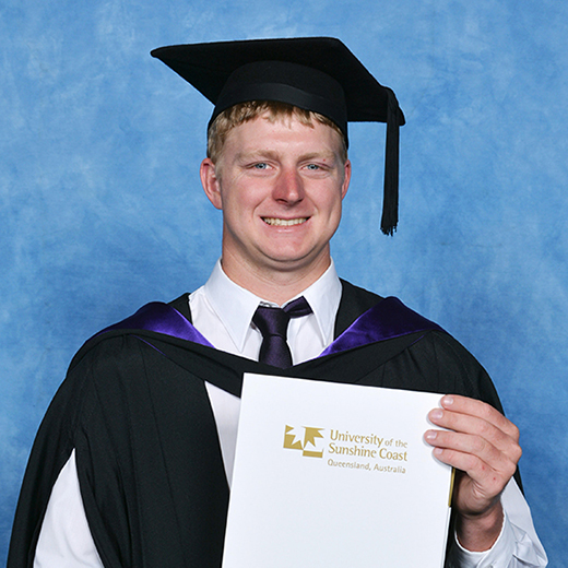 Thomas Krosch wearing graduation gear holding his degree