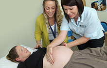 Collaborative Midwifery Clinic facilitator Alison Broderick helping USC student Melanie Williams to assess pregnant mum Meegan Walker.
