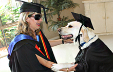 Nicole Damarra and her former Guide Dog, Nev, try on their Graduation gowns