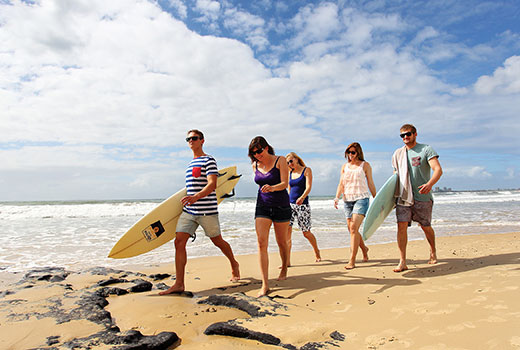 Students walking along beach with surfboards