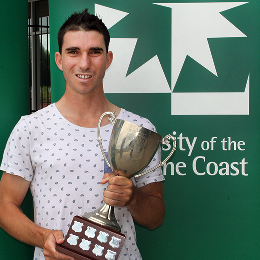 World champion para-cyclist Kyle Bridgwood holding USC's Sportsperson of the Year trophy.