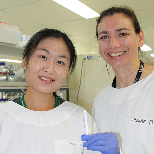 USC PhD student Jia (Jessie) Li and Dr Joanne Macdonald with a test strip that can be used for detecting malaria and dengue.