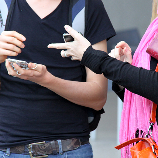A man and a woman holding their smart phones.