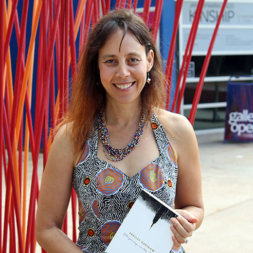 University of the Sunshine Coast academic Shelley Davidow with her book in front of Konstantin Dimopoulos's sculpture 'Pulse' on the USC campus.