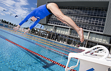 A swimmer dives off the blocks at USC's 10-lane Olympic-standard pool