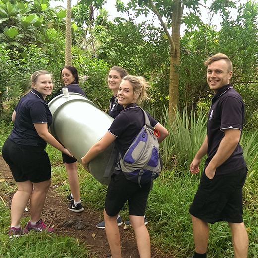 USC students help deliver a rainwater tank in Vanuatu.