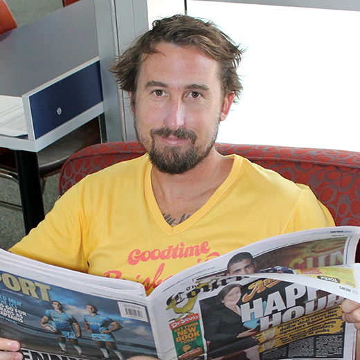 USC Journalism graduate Tom Snowdon reading the newspaper after enjoying a surf on the Sunshine Coast.