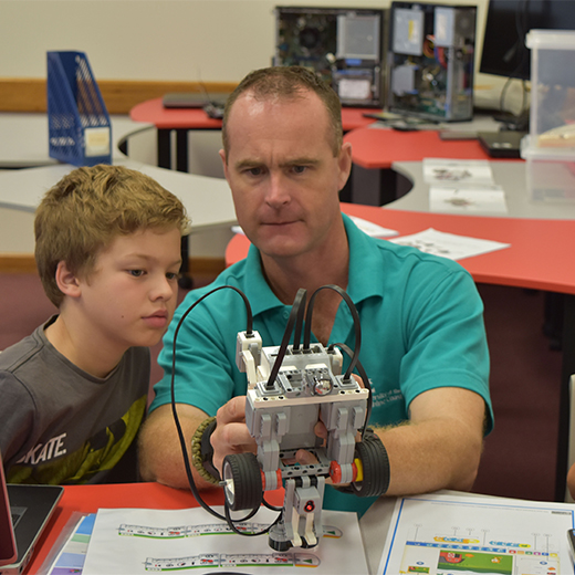 Bachelor of Education student Mathew Wenzel shows Jack Rodda one of the robots used to enhance learning in the new Makerspace Room at USC Fraser Coast.