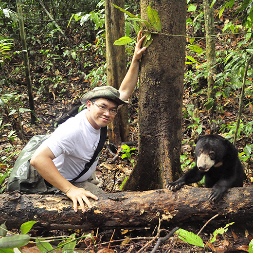 Wong Siew Te with a sun bear in natural habitat.