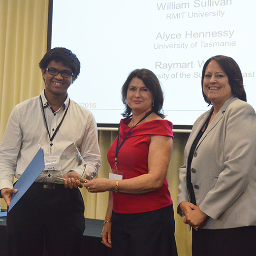 Raymart Walker accepting his award from Sally Rogan and Jennifer DeHaemars at the Australasian PASS and Peer Learning Conference.