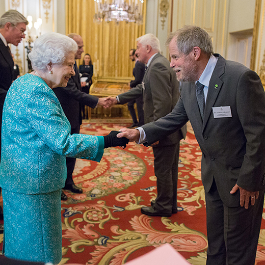 Her Majesty Queen Elizabeth II meets ACIAR Forestry Research Program Manager Tony Bartlett at Buckingham Palace, where a display featured the successful ACIAR-USC research project. Image supplied by ACIAR.
