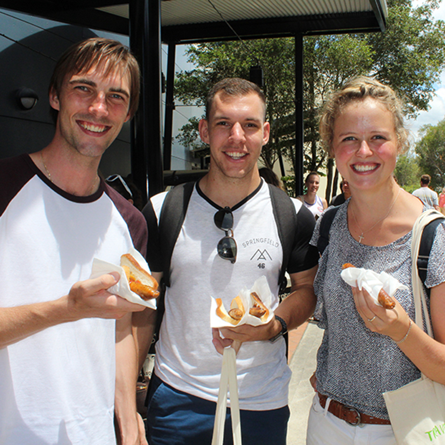 Enjoying the sausage sizzle at USC's Orientation are South African students Roy Langhein and Darryn Dyer and Emma Hough of Zimbabwe.