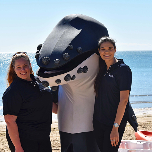USC Tourism, Leisure and Event Management students Lauren Burch and Kerri Hetherington with Fraser Coast mascot, Harvey the Whale.