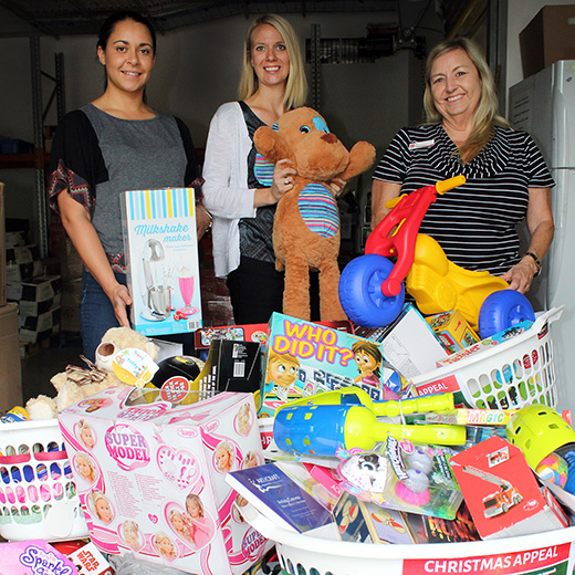 USC staff Amenah Stanford and Sara Kumpf presenting donations to The Salvation Army's Maroochydore Community Engagement Coordinator Dianne Spencer.