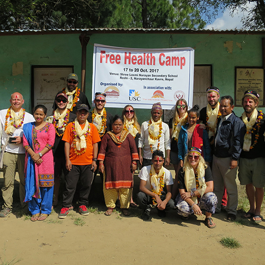 USC Lecturer Robbie King (l) and students join local agency staff to run a health clinic for villagers in Sikhar Ambote, Nepal.