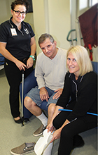 Occupational Therapy students Ange Vitler (right) and Amy Cornelius (standing) work with patient Ray Eisenhut at the Wound Solutions Clinic on campus