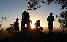 USC Activate club members greet the sunrise after a pre-dawn climb to the peak of Mt Ngungun.