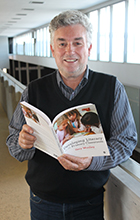 Dr Gary Woolley holds a copy of Developing Literacy in the Primary Classroom